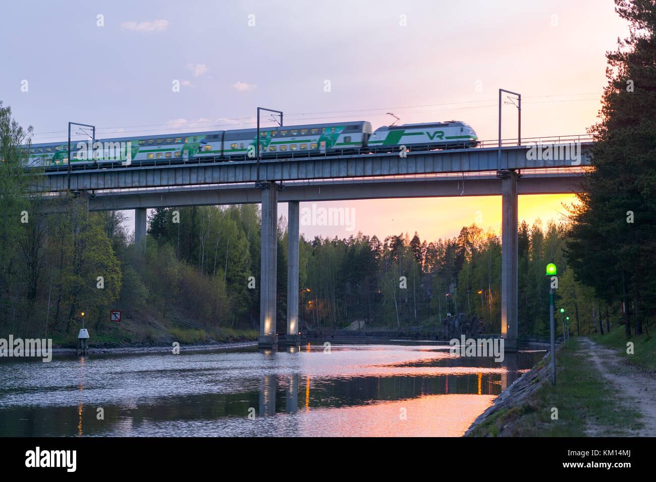 Juna ylittää saimaan kanavan sillan auringonlaskussa - Stock Image