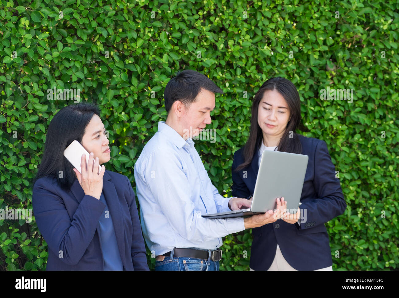 Businesswoman and businessman working outside office using laptop computer mobile phone and tablet device at green - Stock Image