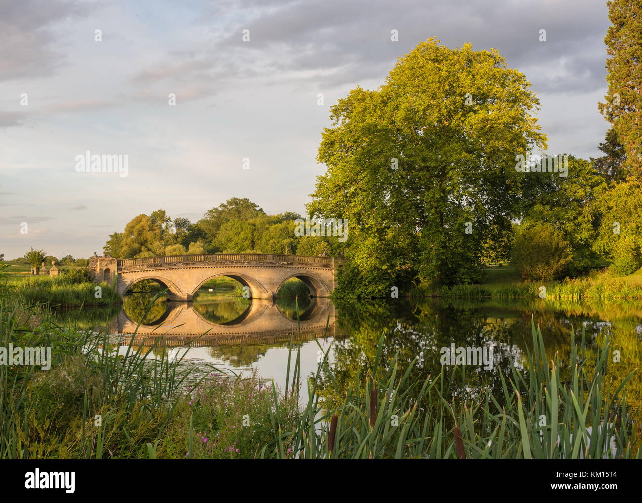 The beautiful sun setting catches a bridge at Compton Verney stately house in Warwickshire - Stock Image