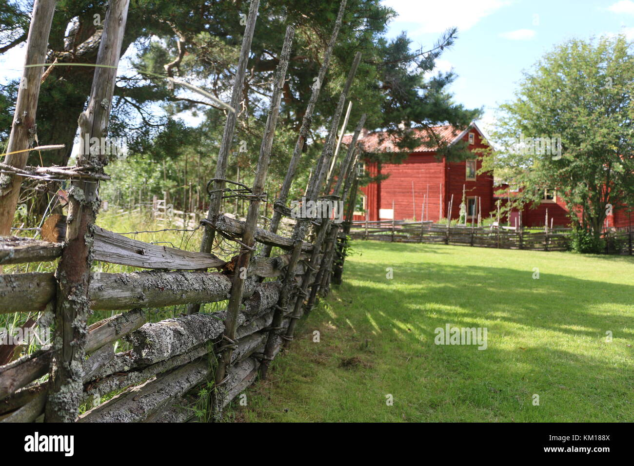 Traditional Swedish wooden fence with red farm house in the background Stock Photo