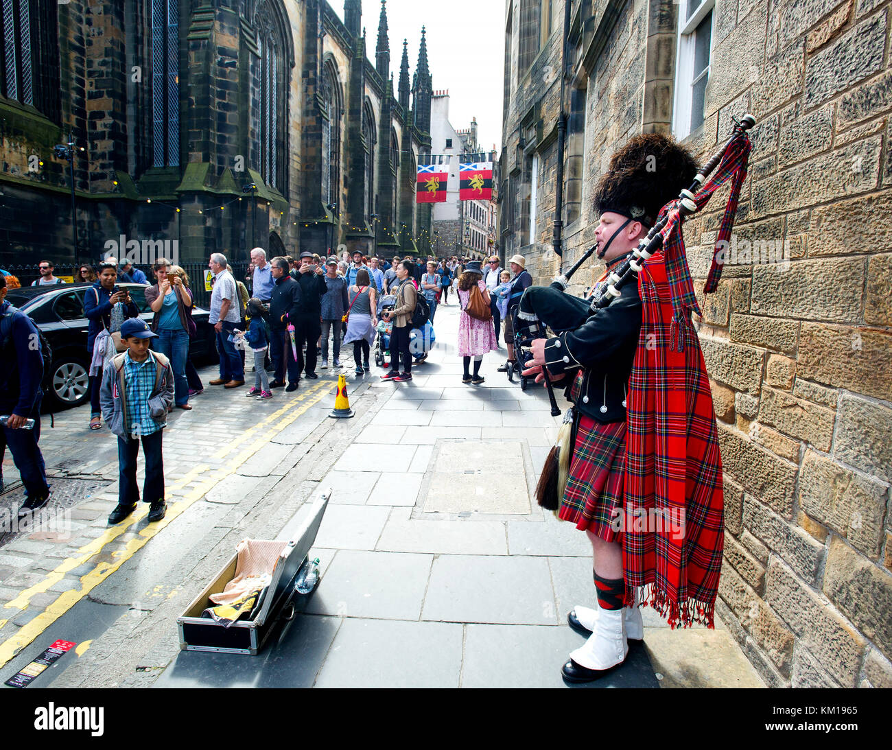 A Scottish piper busking in the Royal Mile, Edinburgh, Scotland. - Stock Image