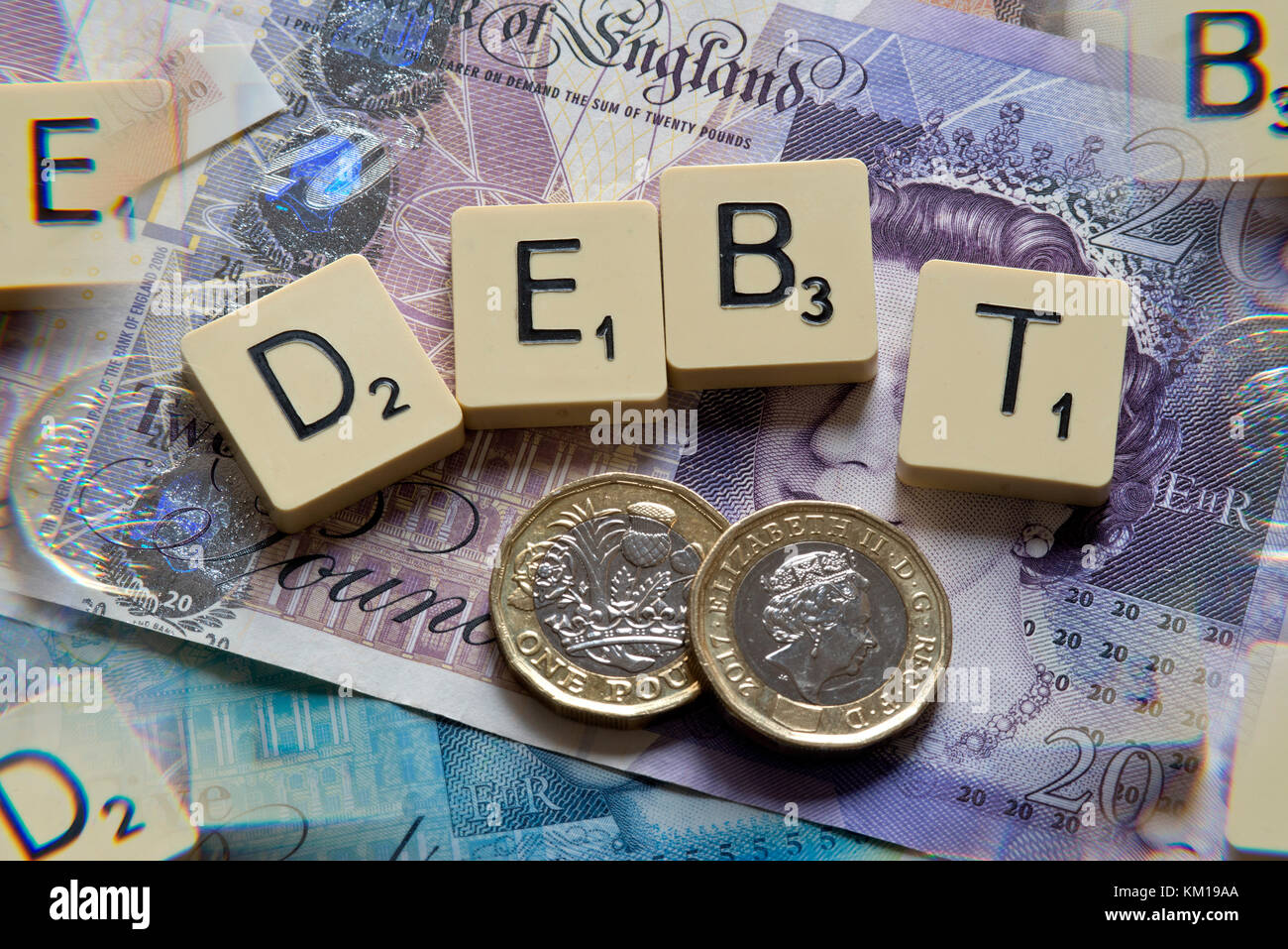Scrabble letters spelling DEBT with new British pounds (GBP) £20, £10, £5 notes and new British pound - Stock Image
