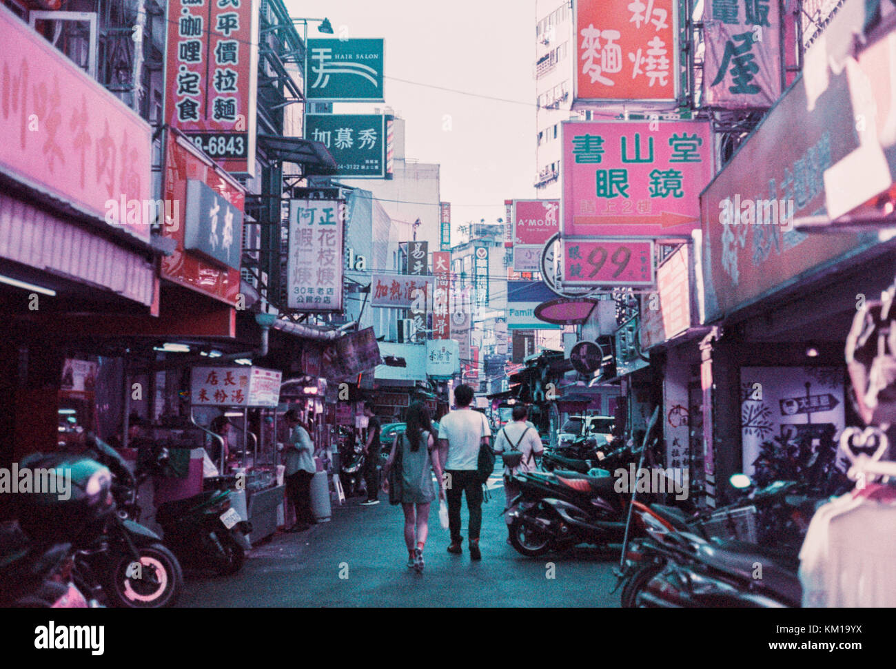 People walking through a surreal, colorful, busy street filled with advertisements in Taipei, Taiwan - Stock Image