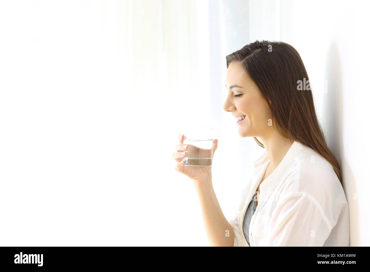 Side view portrait of a happy woman holding a glass of water isolated on white at side - Stock Image