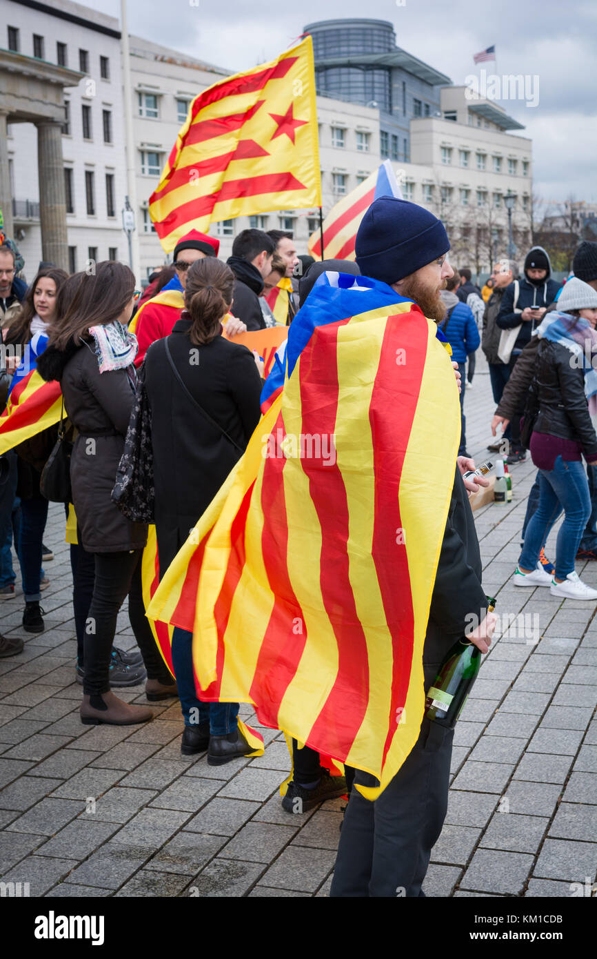 Catalan independence protesters stand as a group in front of the Brandenburg Gate on a cold windy morning in Berlin, - Stock Image