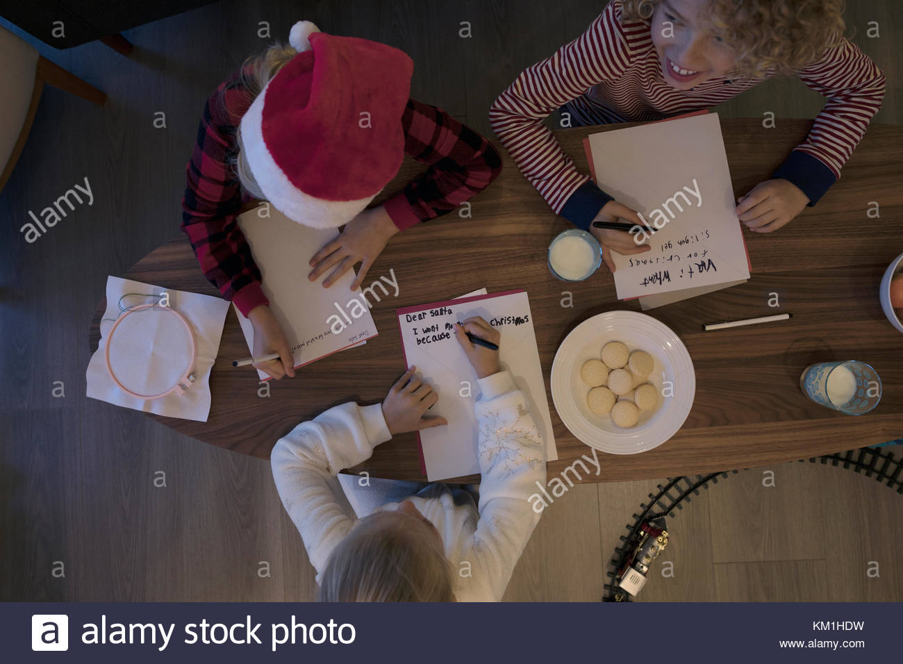 Overhead view brother and sisters writing Santa letters with cookies - Stock Image