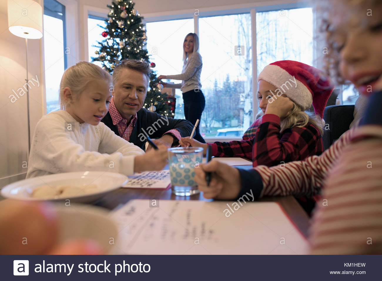 Father watching daughters and son writing Santa letters in Christmas living room - Stock Image