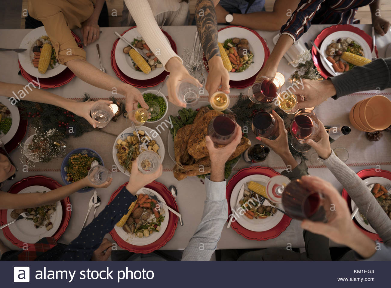 Overhead view family toasting wine glasses at candlelight Christmas turkey  dinner at table - Stock Image