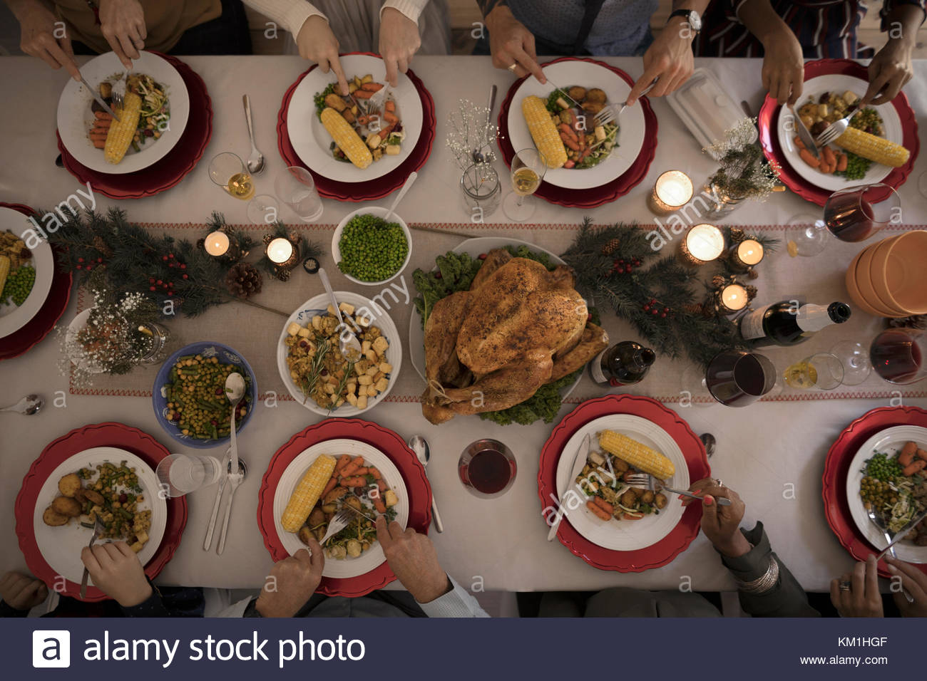 Overhead view family eating candlelight Christmas turkey dinner at table - Stock Image