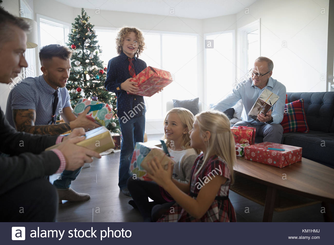 Family opening Christmas gifts in living room - Stock Image