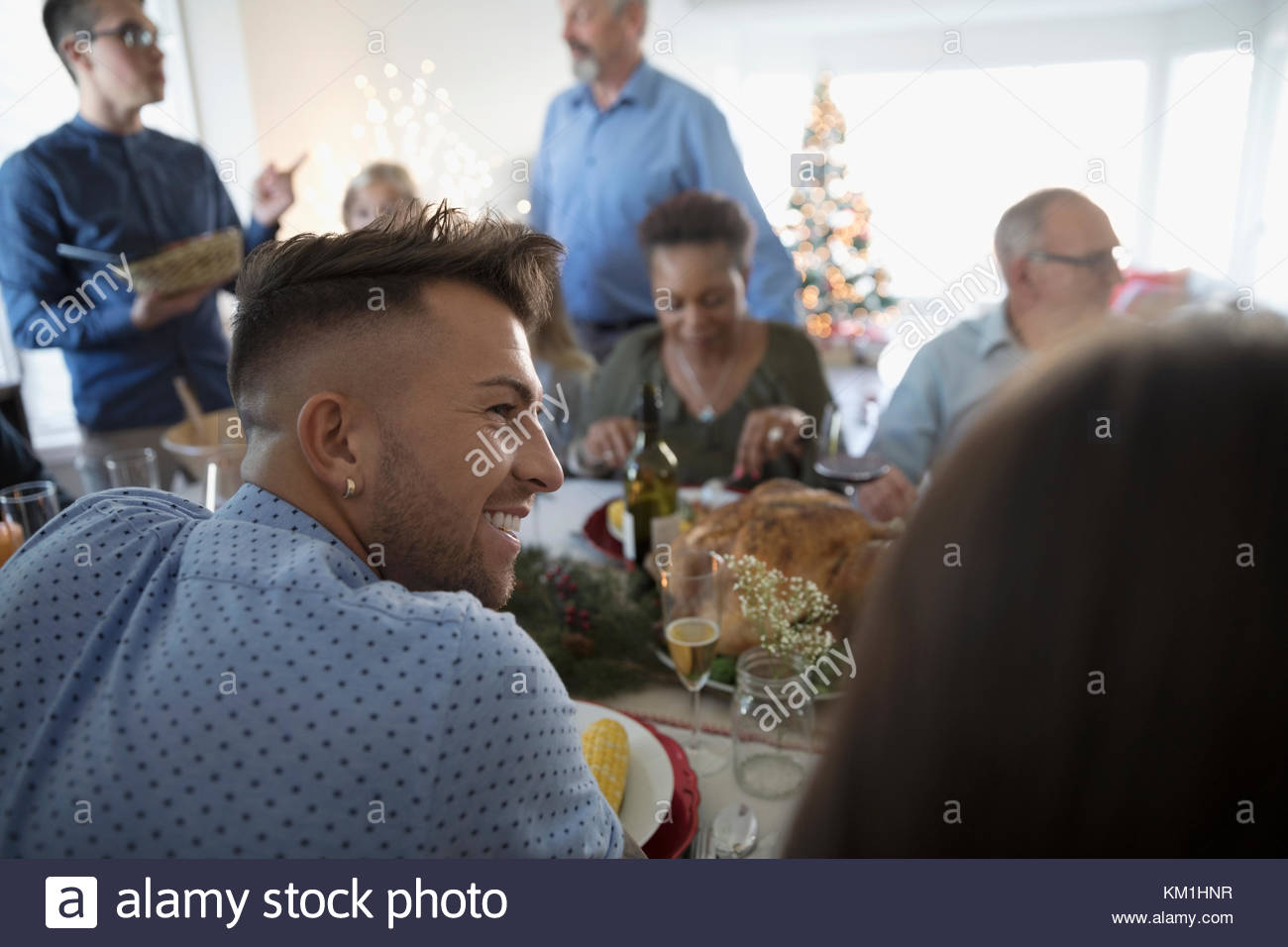 Smiling young man enjoying turkey Christmas dinner with family at table - Stock Image