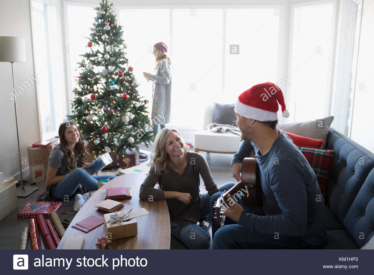 Family playing guitar and wrapping gifts, decorating Christmas tree in living room - Stock Image