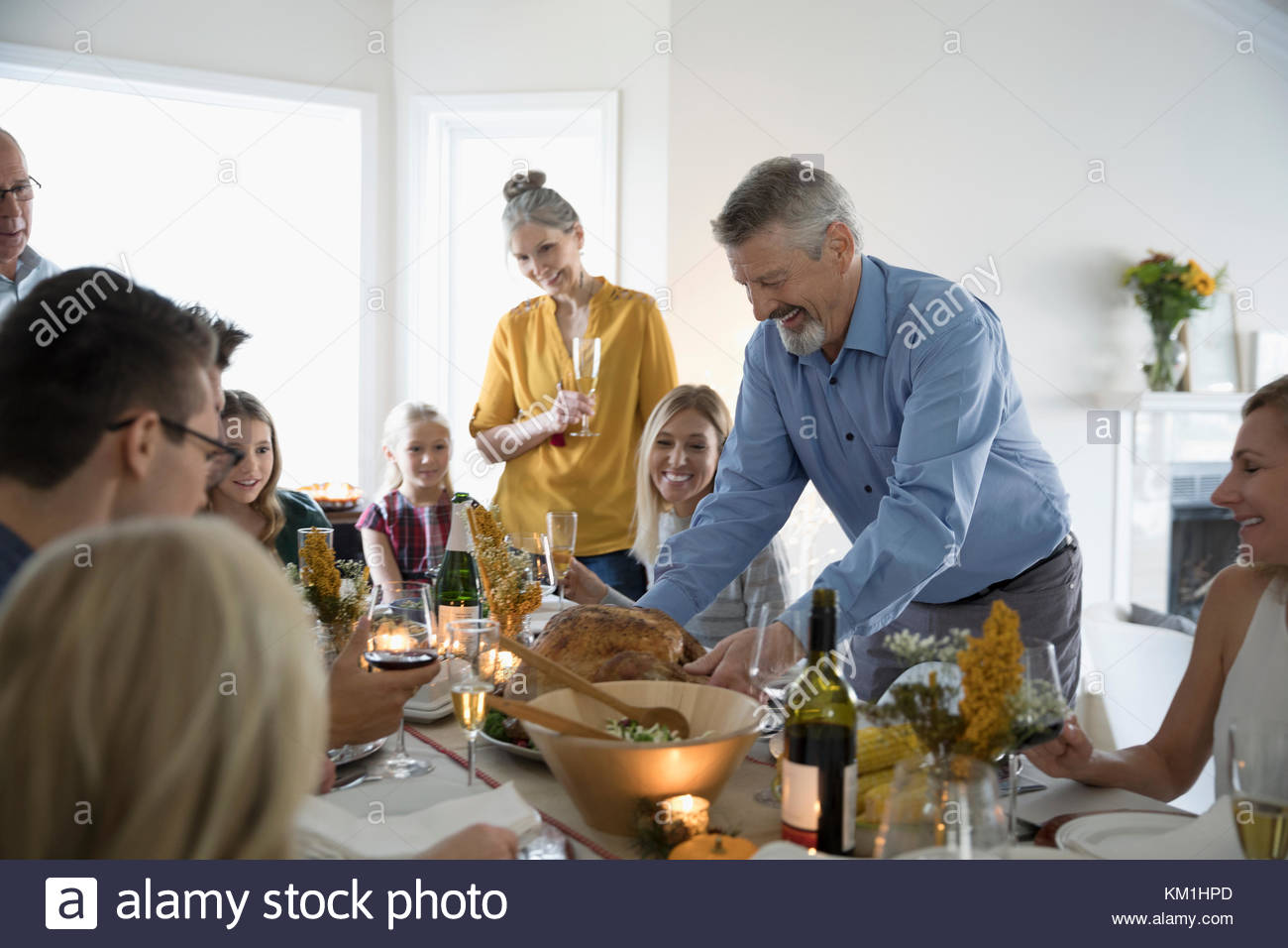Man serving Thanksgiving turkey to family and friends at dinner table - Stock Image