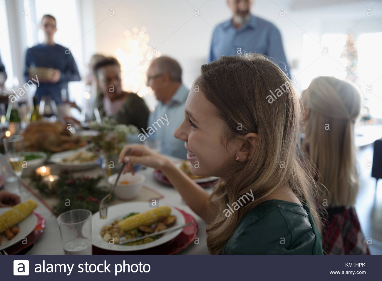 Smiling girl enjoying family Christmas dinner at table - Stock Image