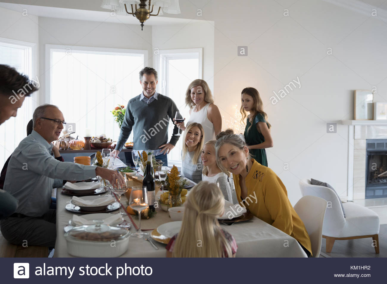 Multi-generation family enjoying Thanksgiving dinner at table - Stock Image