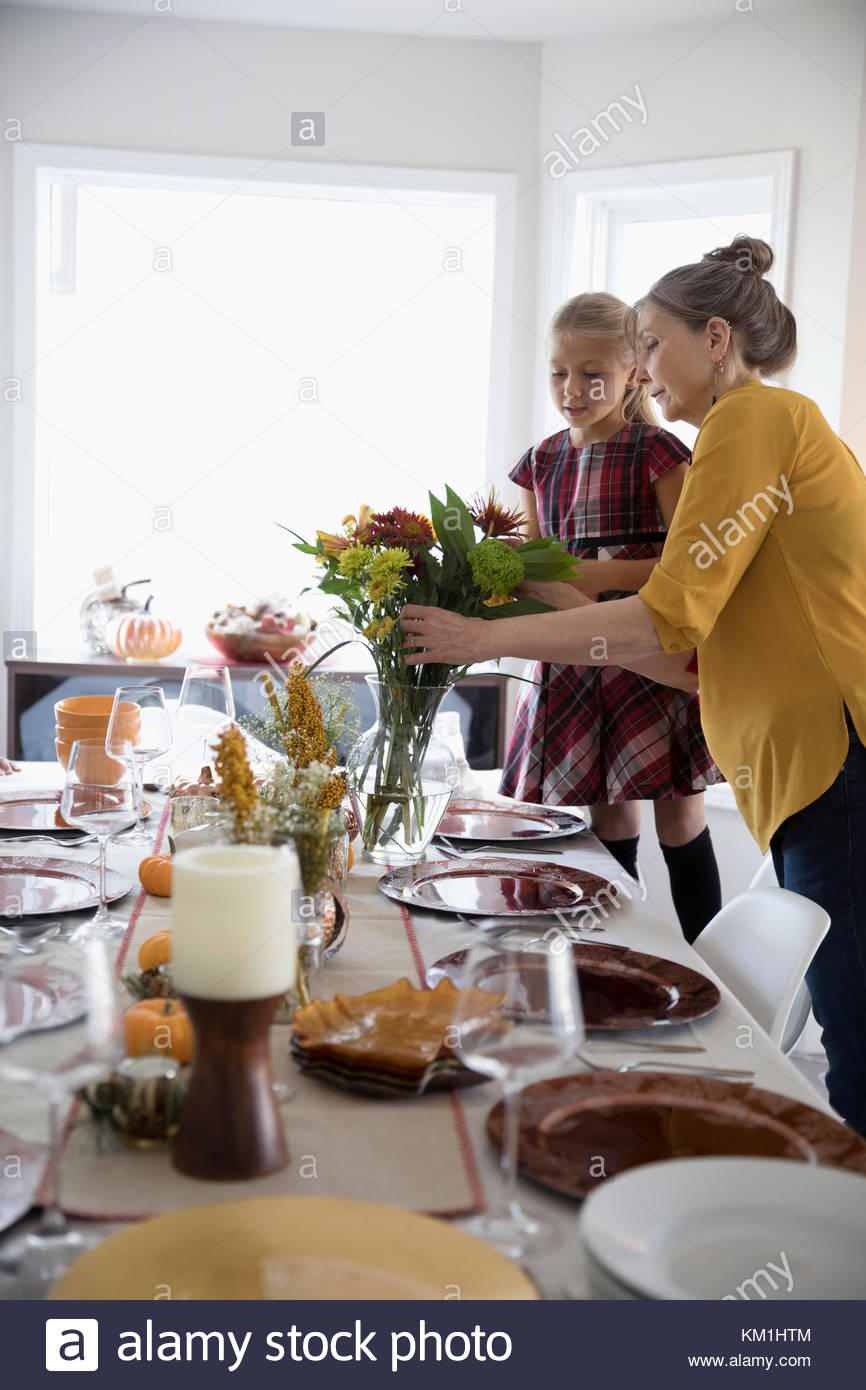 Grandmother and granddaughter arranging flowers and setting the table for Thanksgiving dinner - Stock Image