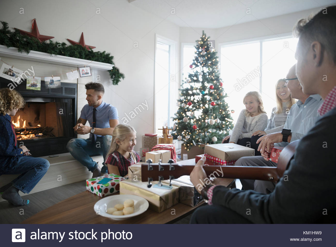 Multi-generation family playing guitar and enjoying fire in Christmas living room - Stock Image