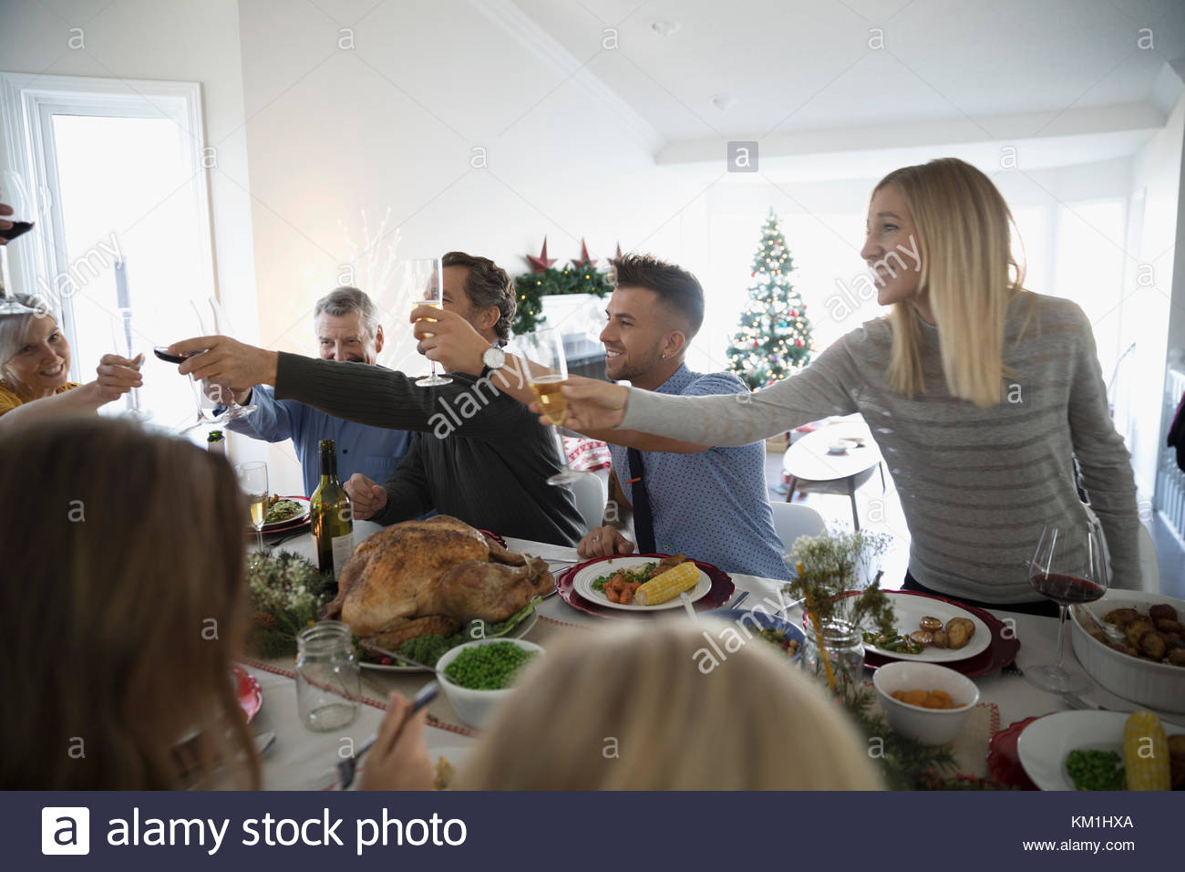 Family and friends toasting champagne glasses at turkey Christmas dinner table - Stock Image
