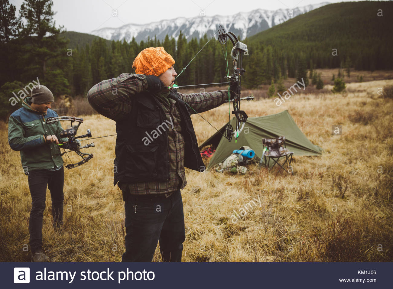 Male hunter friends aiming hunting compound bows outside tent at campsite in remote field below mountains - Stock Image