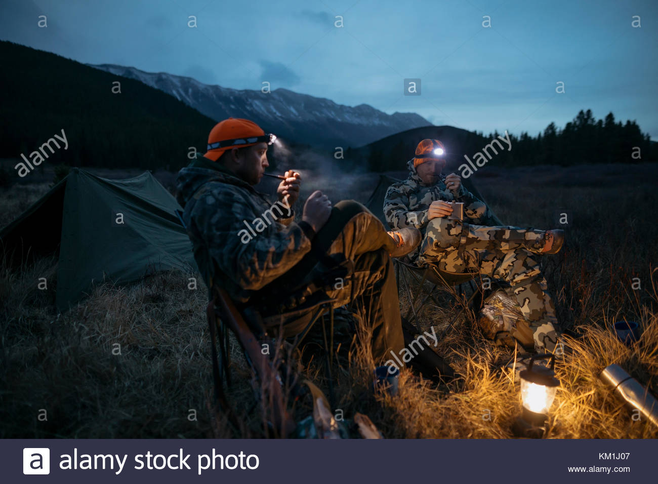 Male hunter friends in headlamps smoking pipes at campsite in remote field below mountains at night - Stock Image