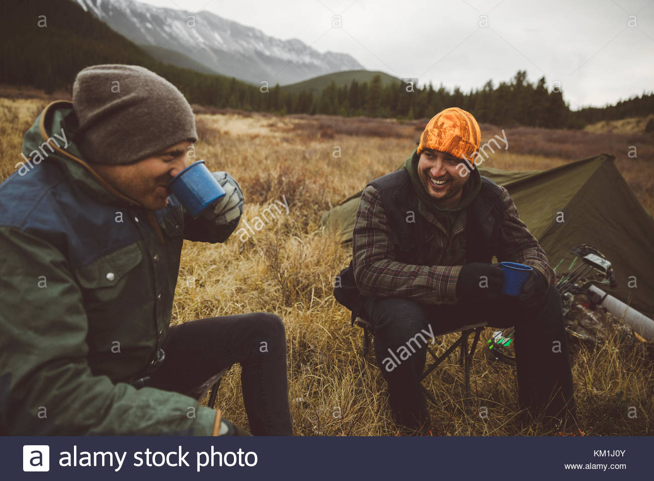 Smiling male hunter friends drinking coffee outside tent at campsite in remote field below mountains Stock Photo