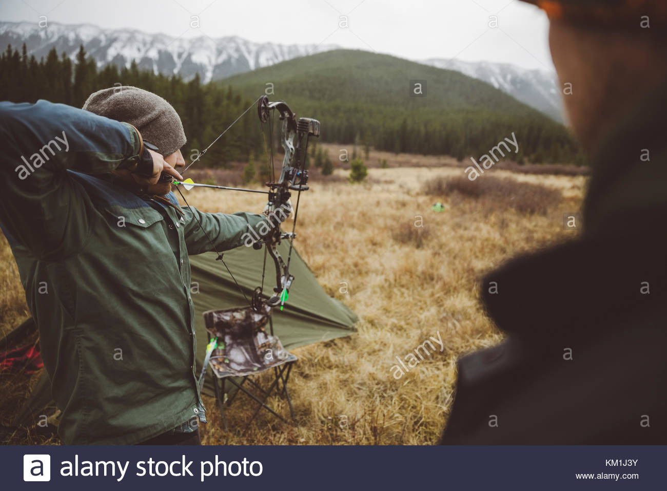 Male hunter aiming hunting compound bow in remote field below mountains - Stock Image