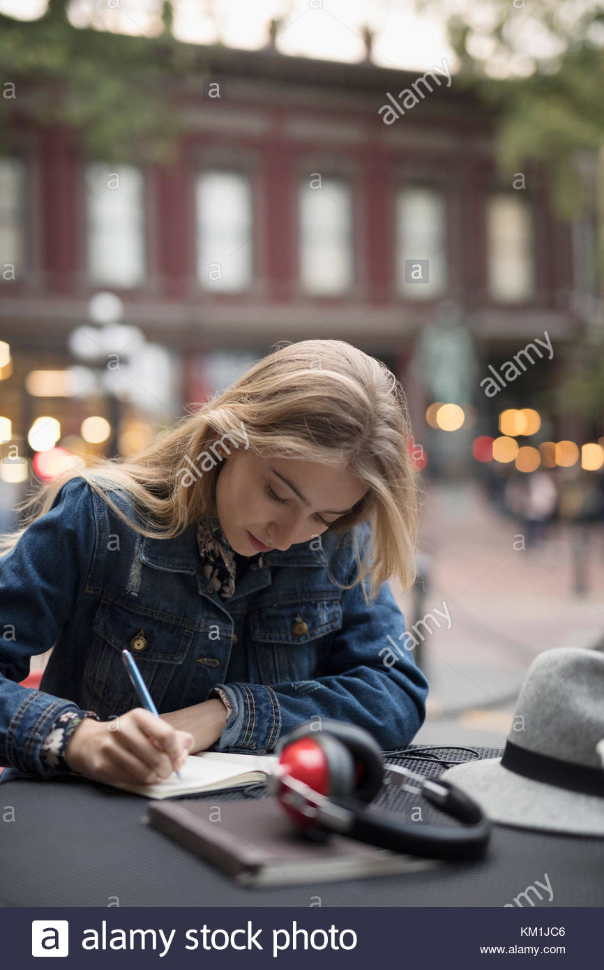 Blonde young woman writing in journal at sidewalk cafe - Stock Image