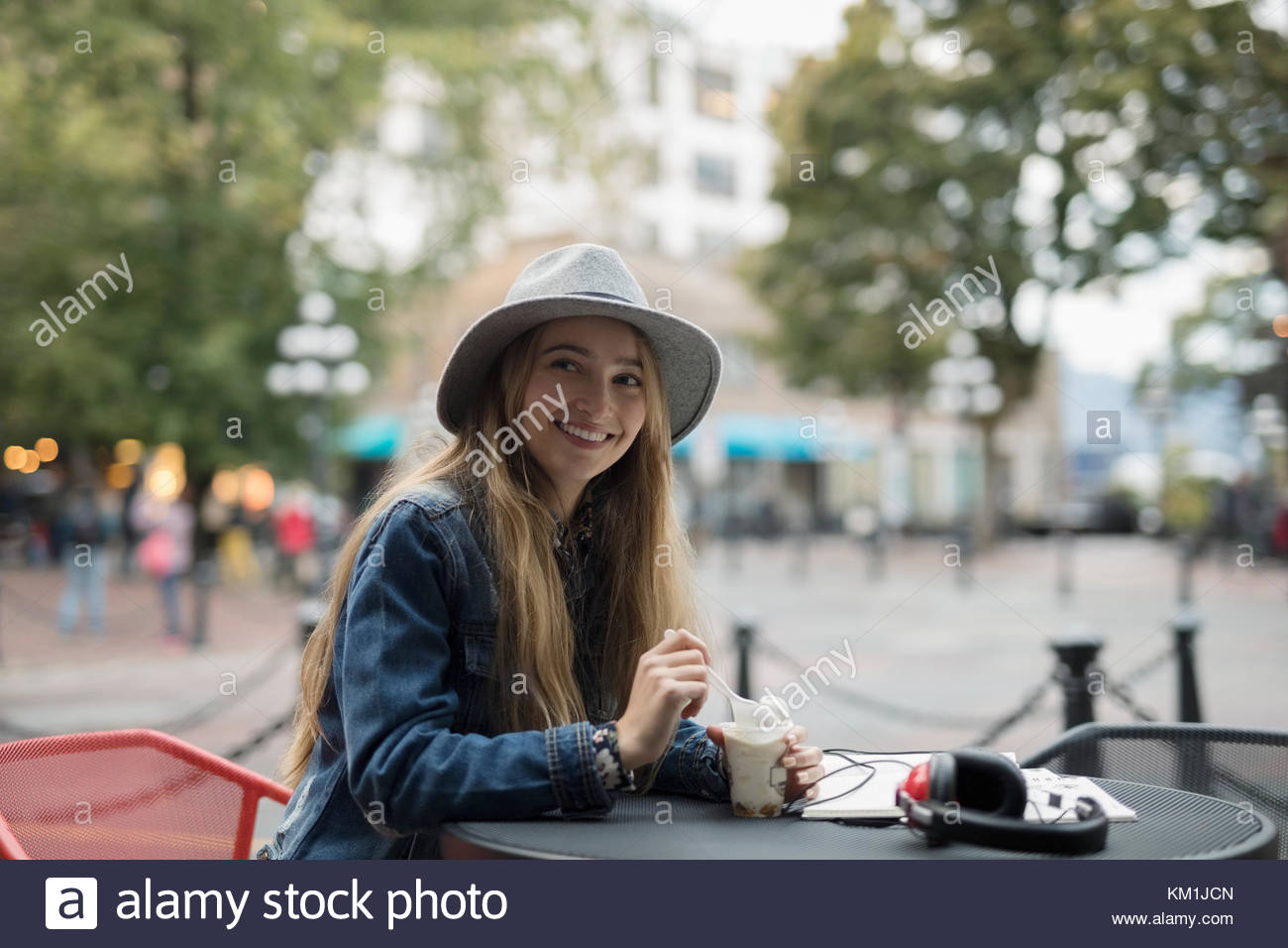 Portrait smiling young woman eating ice cream at urban sidewalk cafe Stock Photo