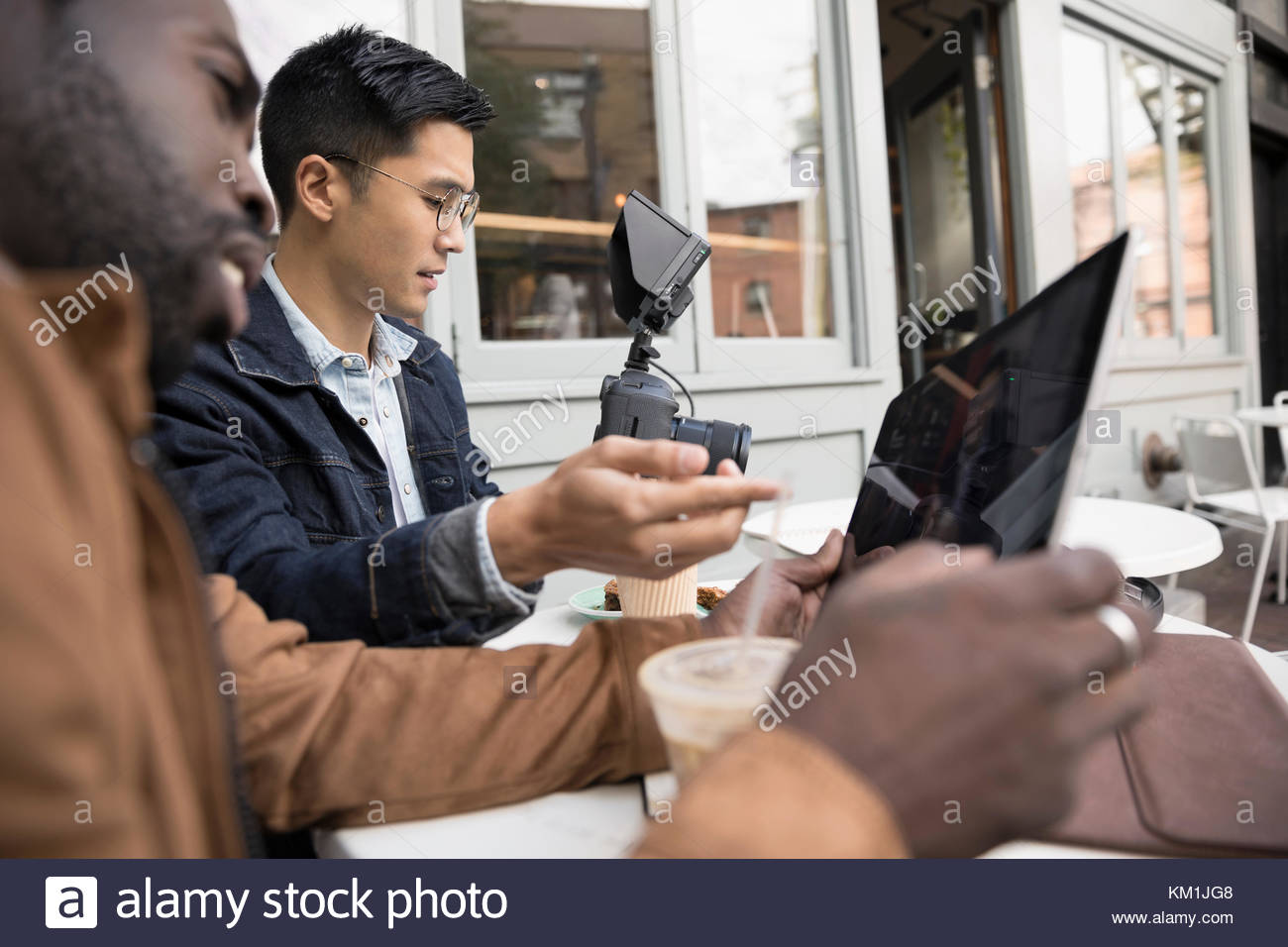 Men friends vlogging, watching video on digital camera at sidewalk cafe - Stock Image