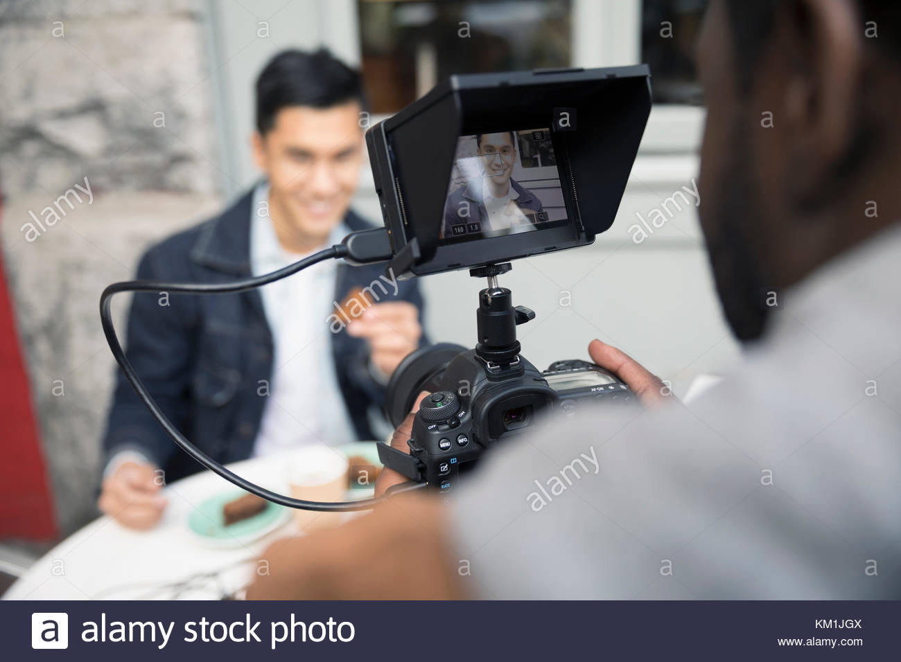 Man vlogging, videoing friend eating at sidewalk cafe with video camera - Stock Image