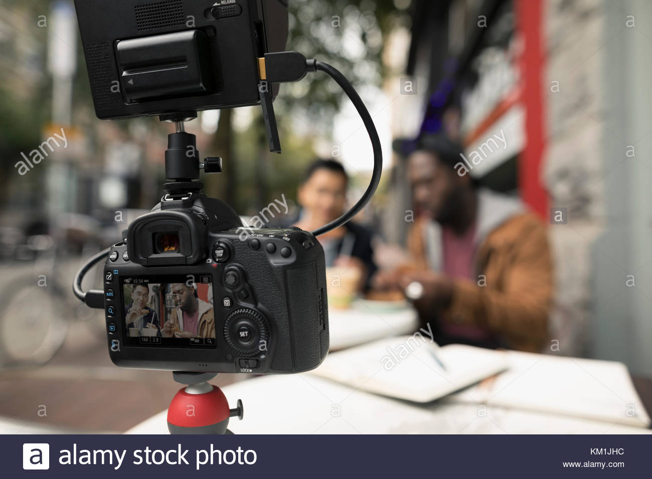 Men vlogging with video camera, eating at urban sidewalk cafe - Stock Image