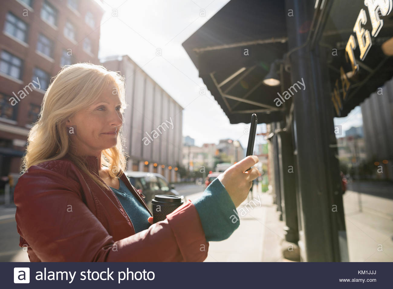Mature woman with coffee using camera phone at sunny urban window storefront - Stock Image