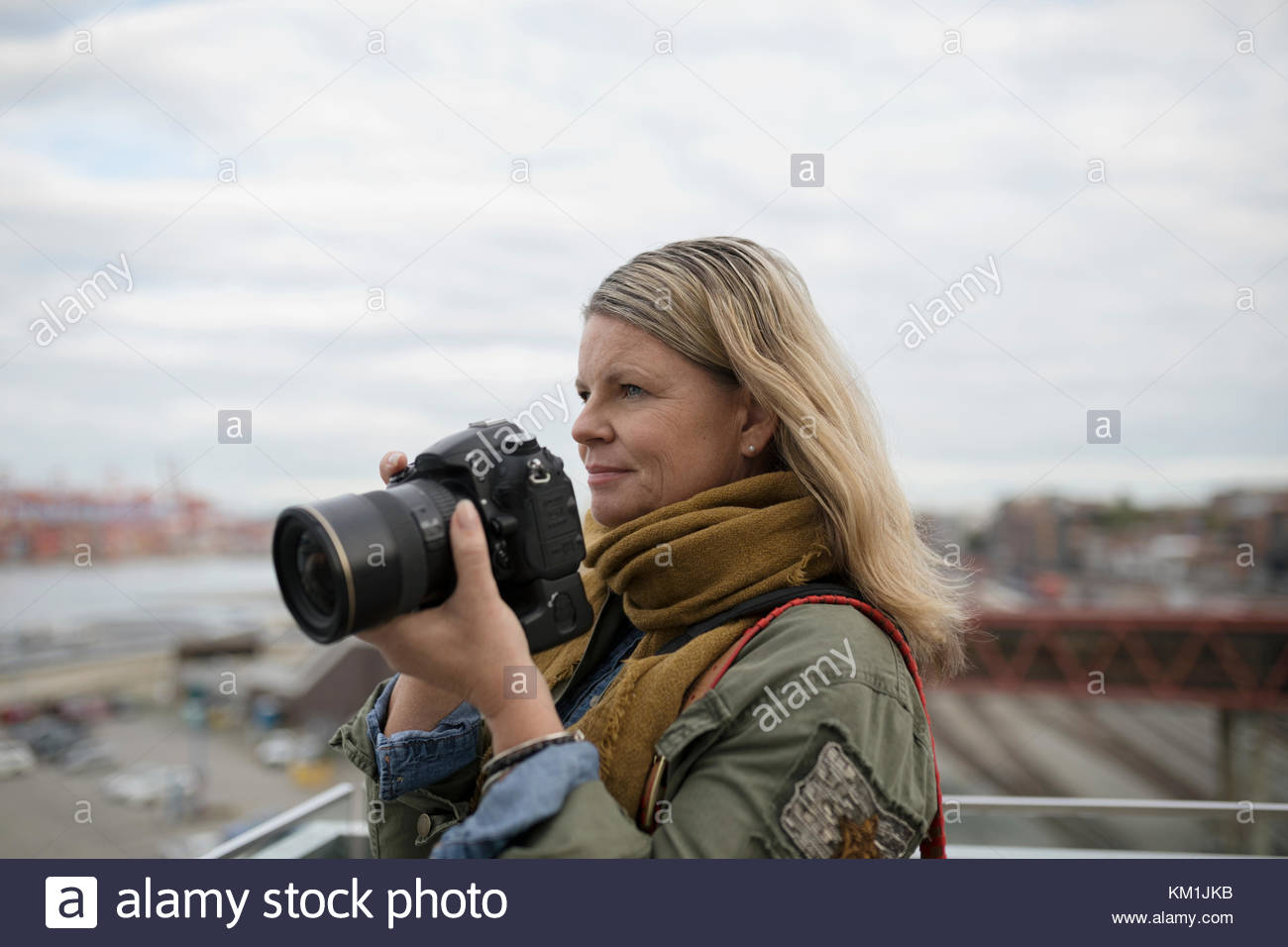 Mature woman photographing with digital camera - Stock Image