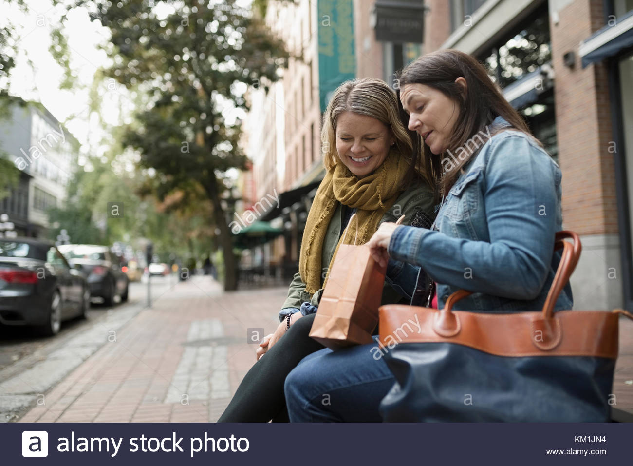 Mature women friends looking into shopping bag on urban sidewalk bench - Stock Image