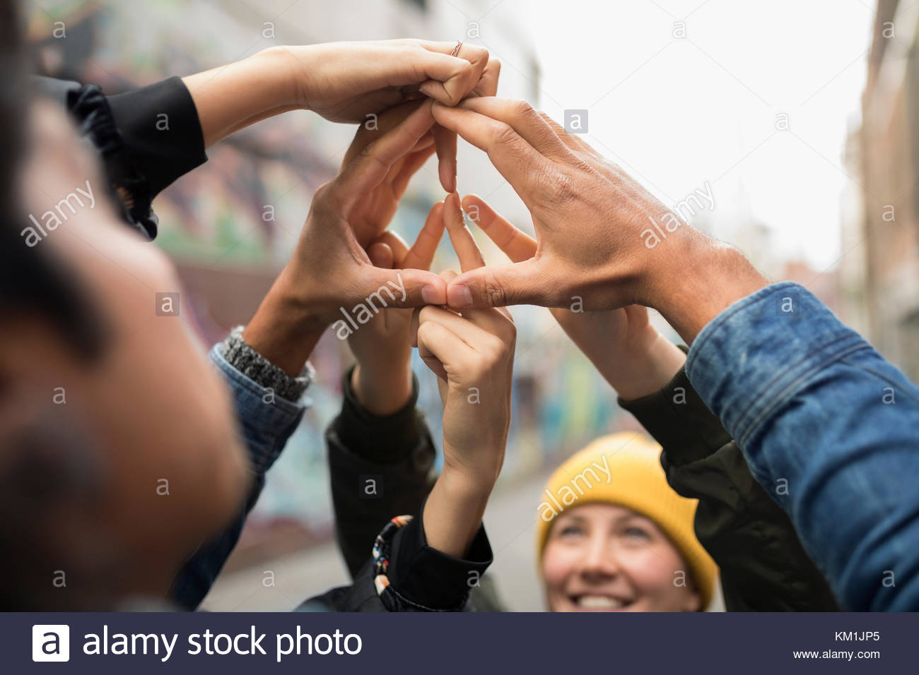Friends forming peace sign with hands - Stock Image