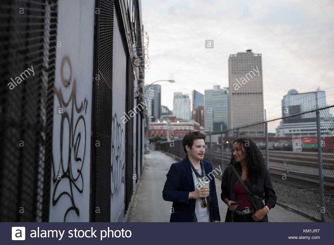 Young couple walking along urban railroad tracks - Stock Image