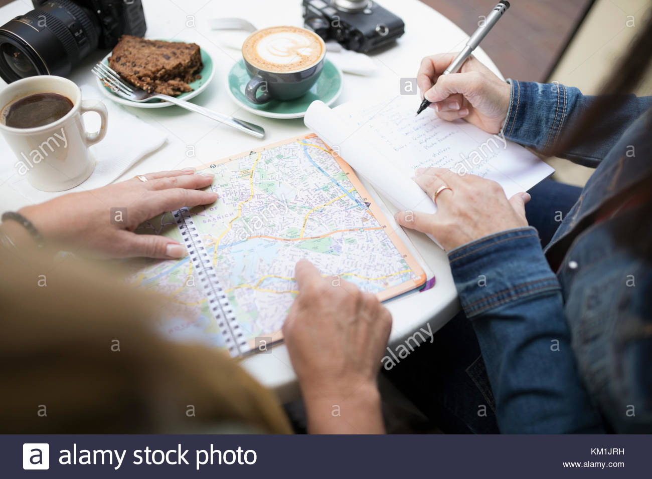 Women friends planning with map, drinking coffee at sidewalk cafe - Stock Image