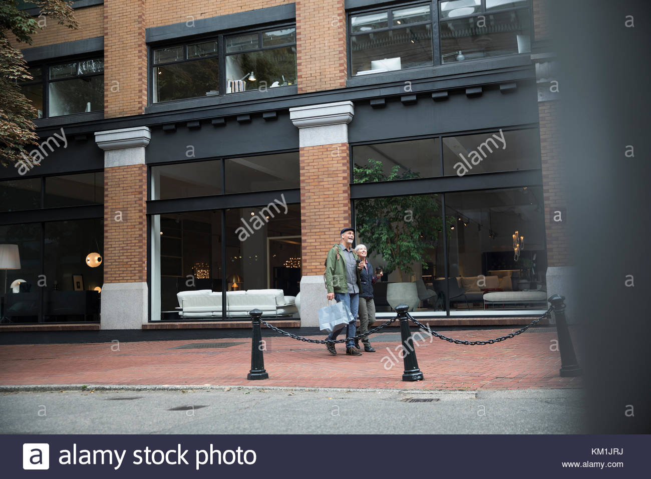 Senior couple walking on urban sidewalk past storefronts - Stock Image
