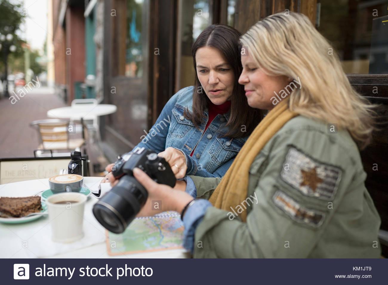 Mature women looking at digital camera viewfinder at sidewalk cafe - Stock Image