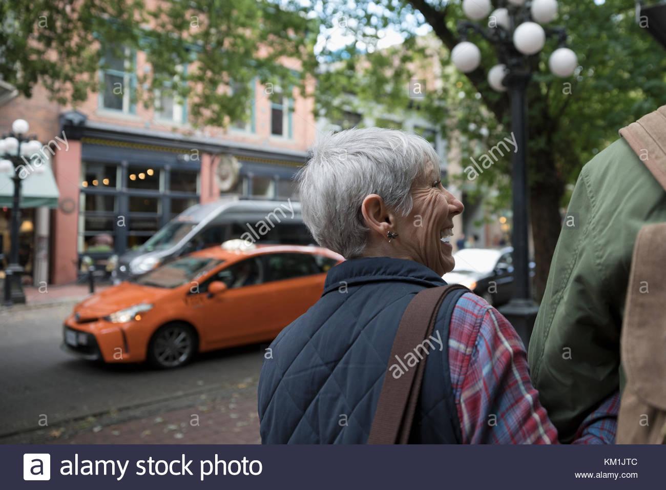 Smiling senior couple walking on urban sidewalk - Stock Image
