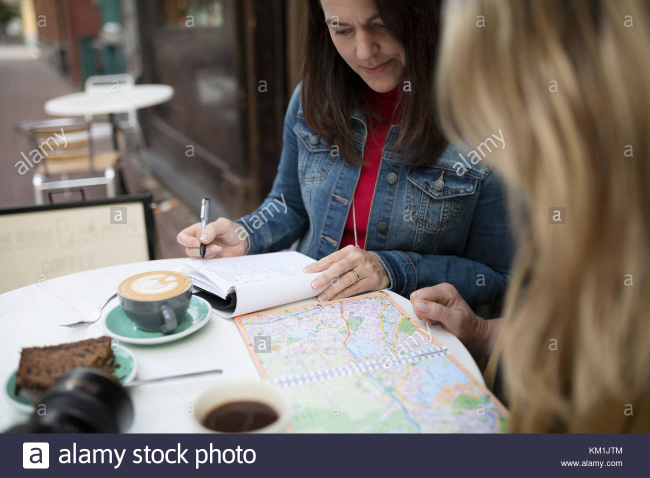 Mature women friends planning with map, drinking coffee at sidewalk cafe - Stock Image
