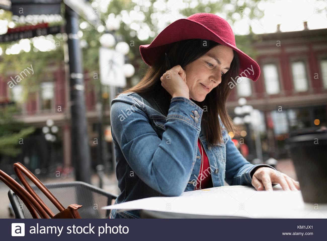 Mature woman in hat looking at map at urban sidewalk cafe - Stock Image