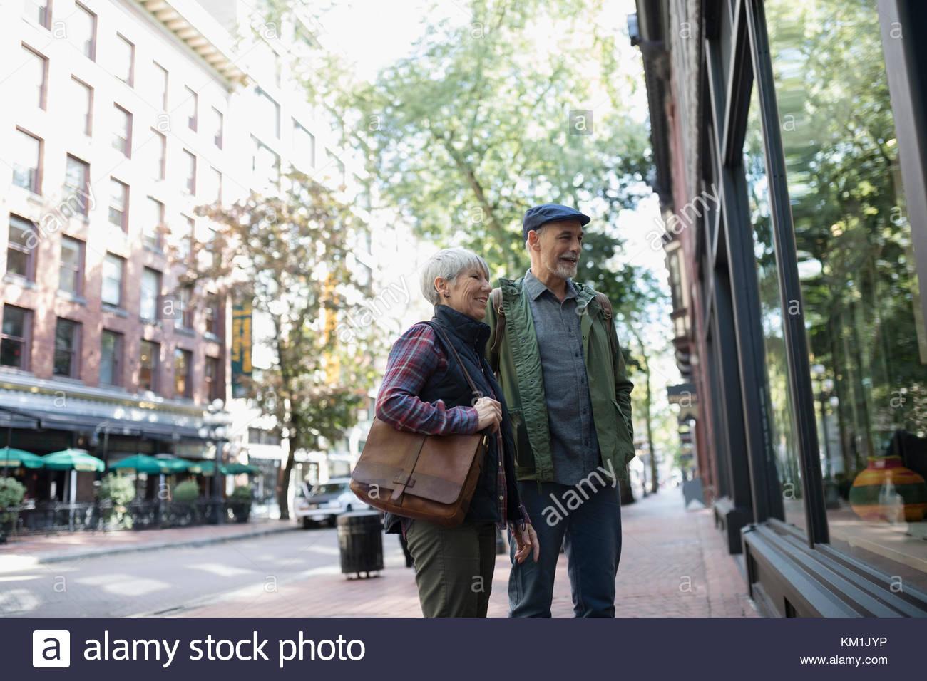 Senior couple window shopping at urban storefront - Stock Image