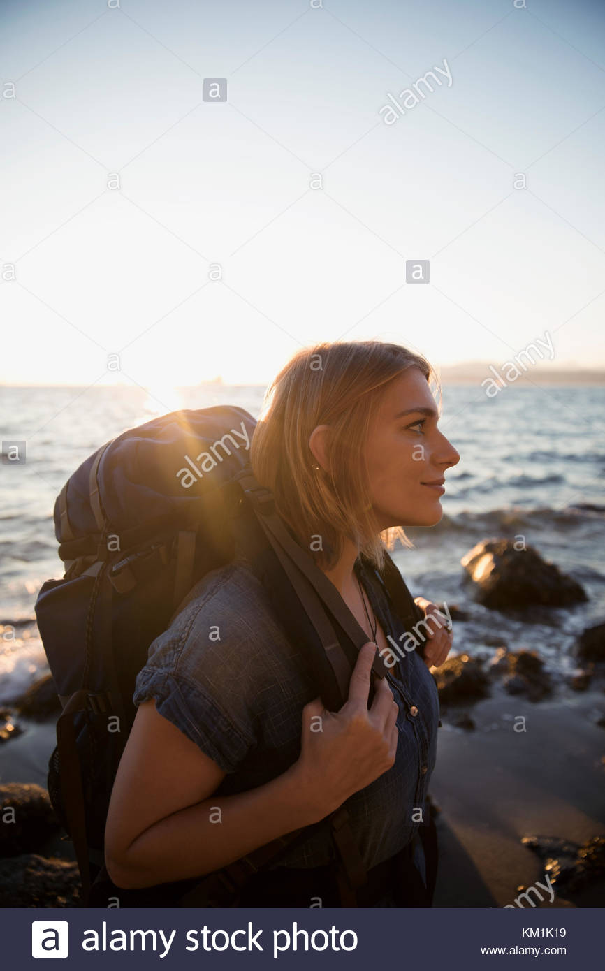 Pensive woman with hiking backpack walking on sunny ocean beach - Stock Image