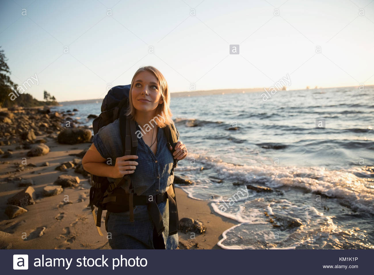 Curious woman with hiking backpack looking up on sunny ocean beach - Stock Image