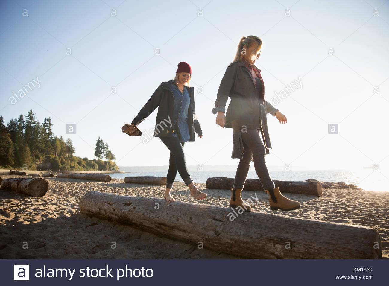 Mother and daughter walking, balancing on log on sunny ocean beach - Stock Image