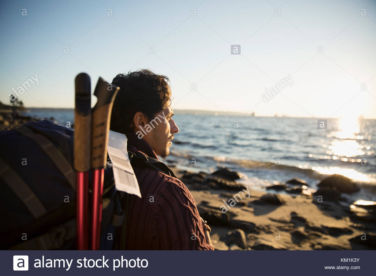 Man with hiking backpack looking at sunny ocean view - Stock Image