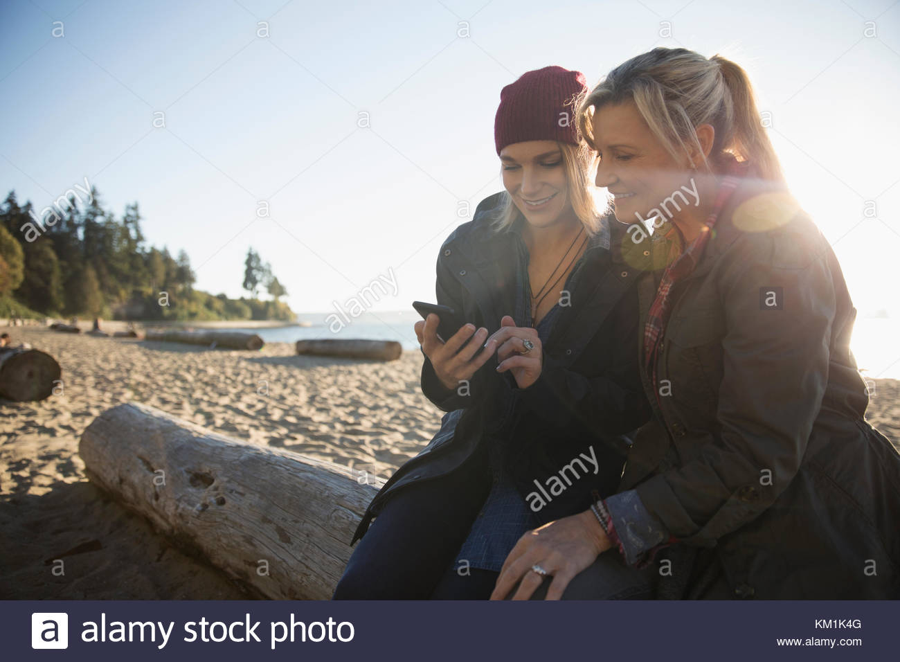 Mother and daughter using smart phone on sunny ocean beach - Stock Image