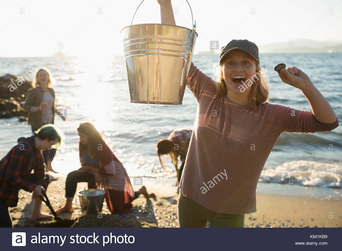Portrait enthusiastic girl with bucket digging for mussels with family on sunny ocean beach Stock Photo