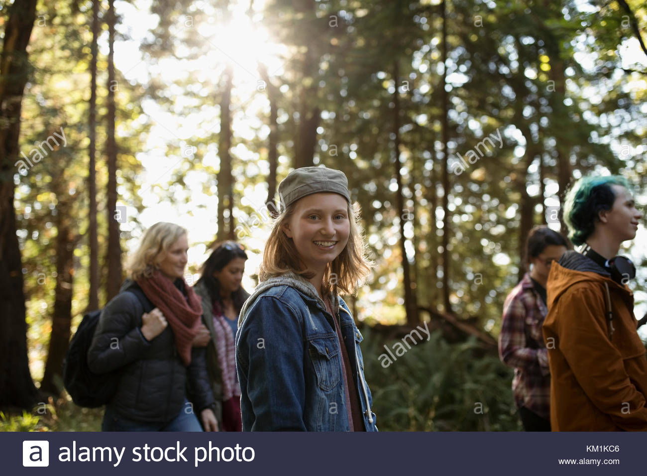 Portrait smiling girl hiking in woods with family - Stock Image